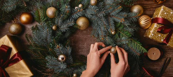 making christmas decoration at wooden table